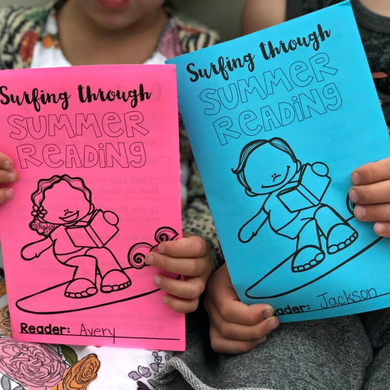 kids holding up summer reading activity booklets