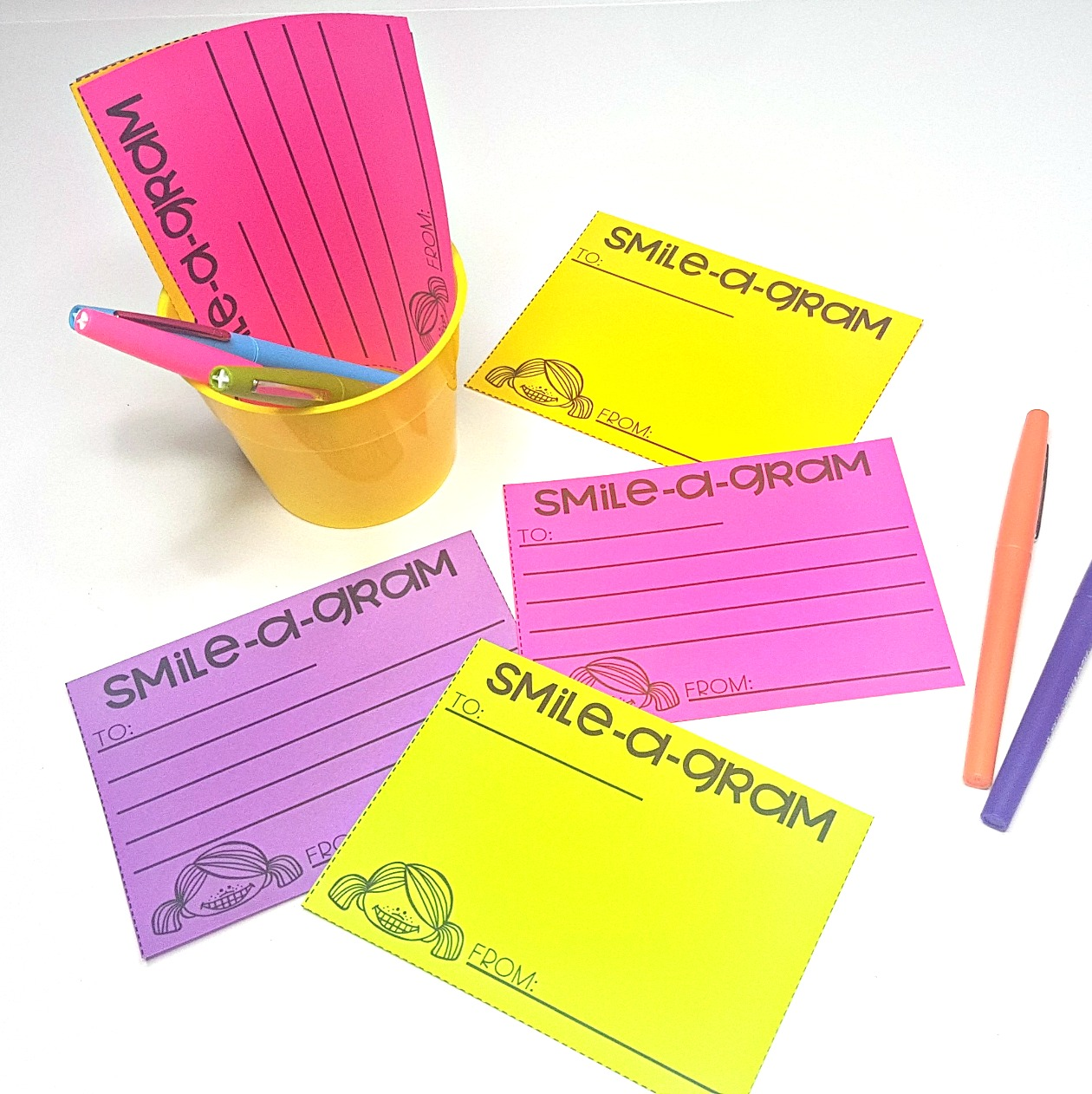 smile-a-gram kindness note card on table with pens