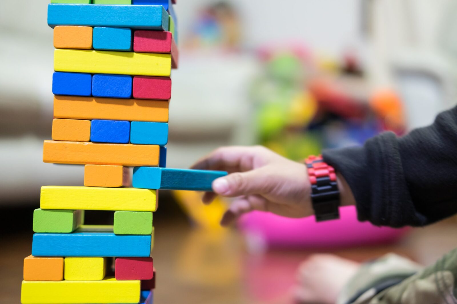 colored blocks stacked up with a child taking one away