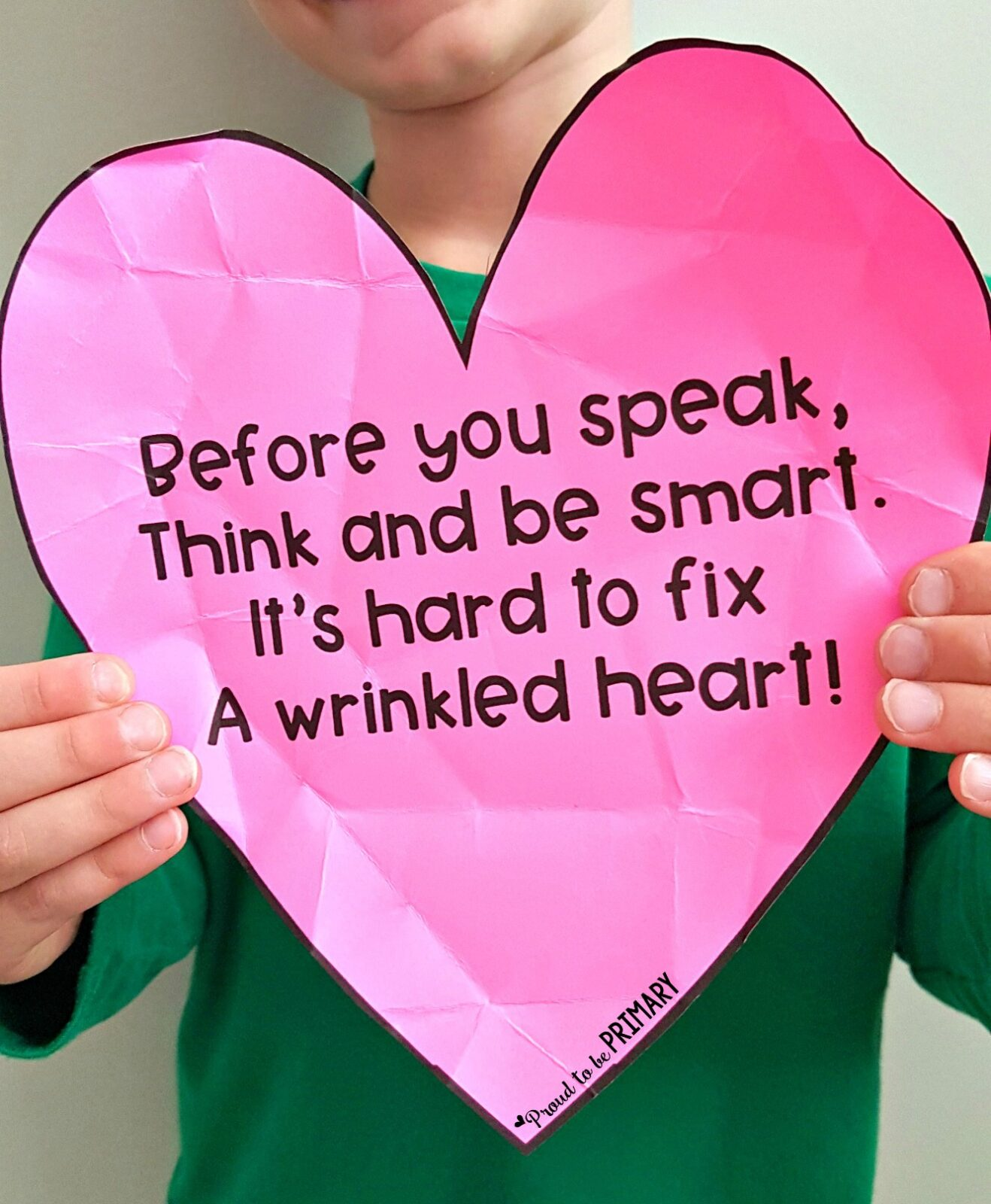 child holding up wrinkled heart for empathy activity and poem