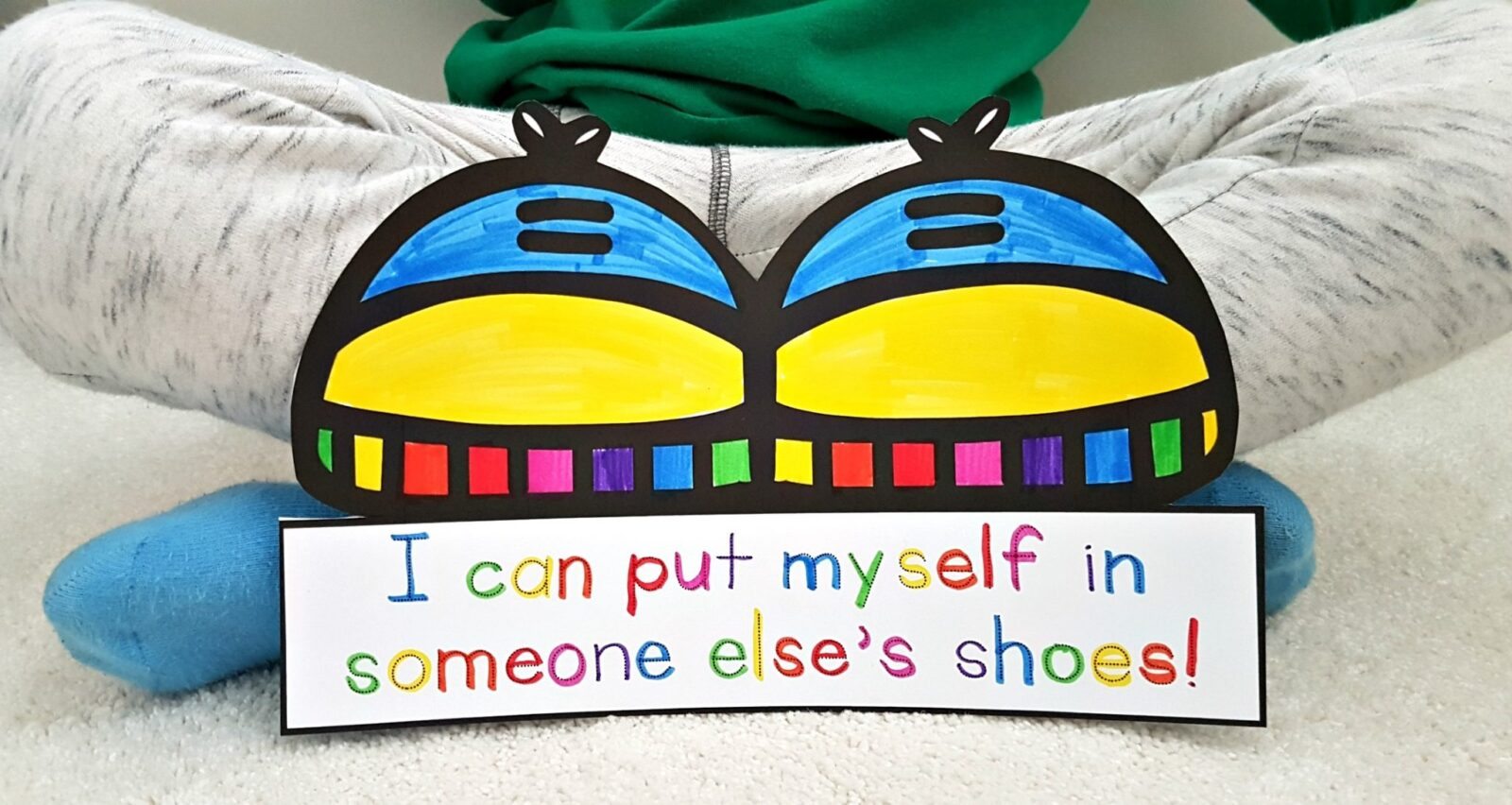 teaching empathy skills - shoe craft with colored quote leaning against a child's legs