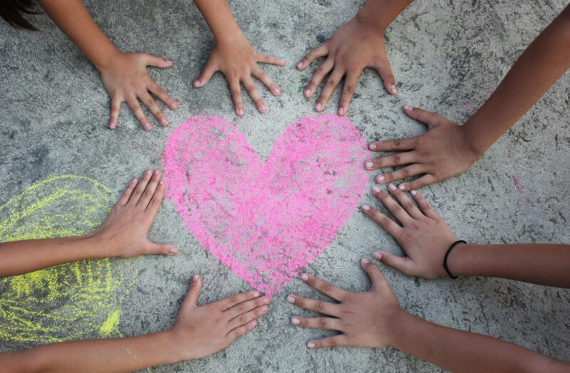 hands on the ground around a chalk heart - social-emottional leaning activities