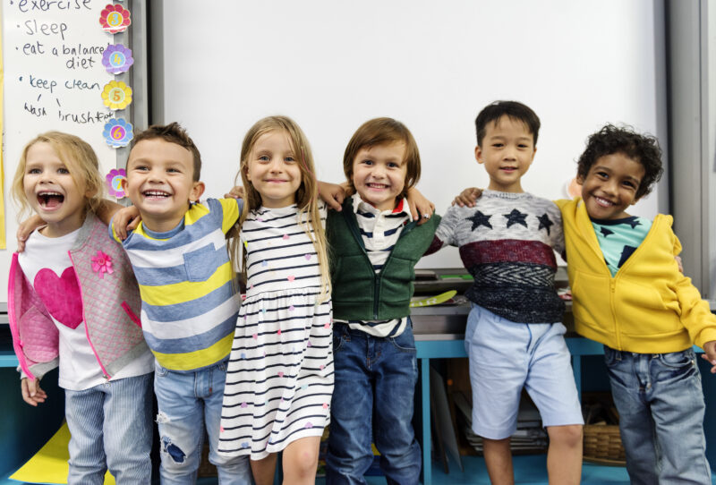 group of kids standing arm in arm smiling in the classroom