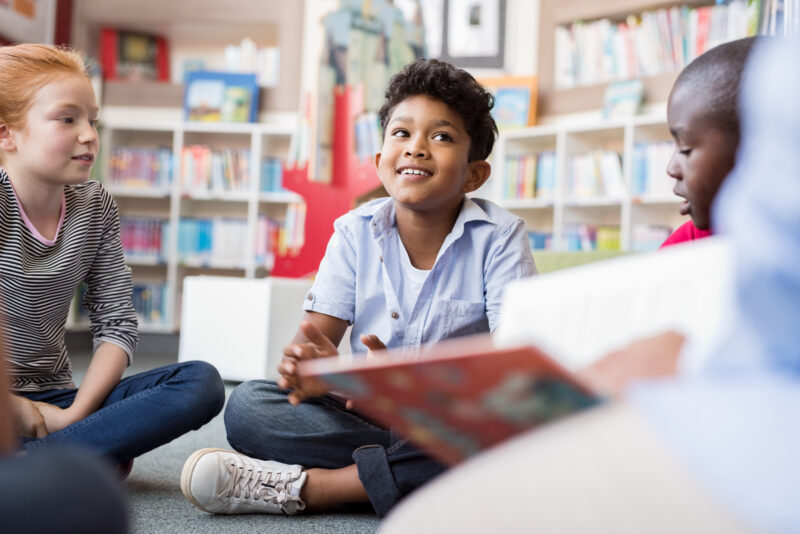 smiling kid looking at teacher with an open book during morning meeting