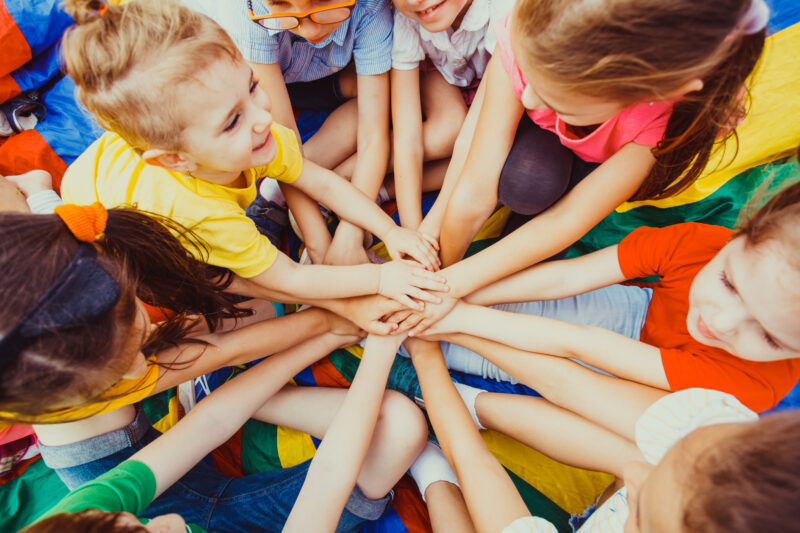 group of kids putting their hands on top of each other in a circle