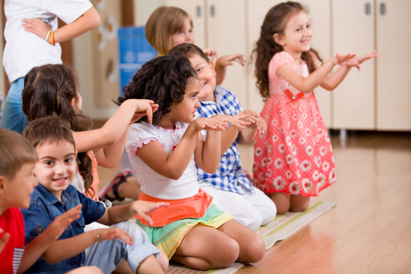 group of kids moving their hands while kneeling at the carpet during morning meeting